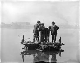 [Three men, including Distribution Engineer Mr. Busch (in bowler hat), on float in False Creek co...