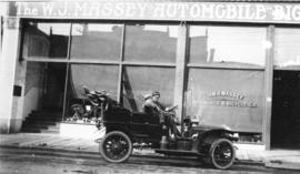[Men in a car outside The W.J. Massey Automobile and Bicycle Company]