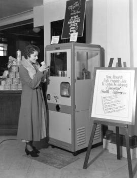 [Woman using pineapple juice vending machine at the Hudson's Bay store]