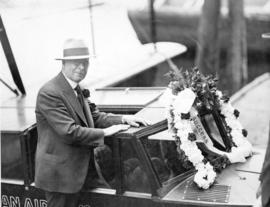 "[Mayor L.D. Taylor getting into boat with wreath of flowers and ""success"" ribbon on the..."