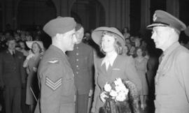 [Anna Neagle talking with two air cadets]