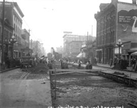 [Men laying streetcar tracks at Granville and Helmcken Streets, for reconstruction of Granville S...