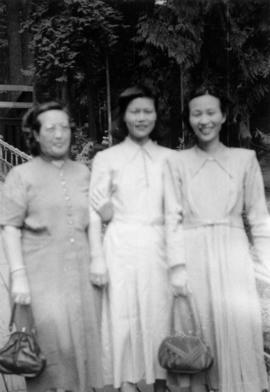 Lillian Ho Wong, Mrs. Chan, and Gum May Yee on a pedestrian bridge in a park