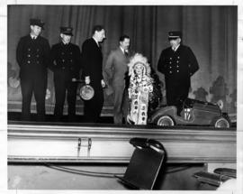 Beverly Kendall, wearing First Nations dress, as 1936 Vancouver Jubilee mascot, on stage with fir...