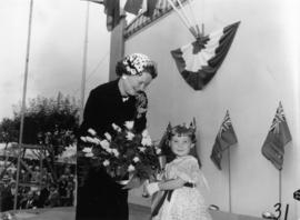 Girl presenting unidentified female dignitary with flowers on Outdoor Theatre stage during 1955 P...
