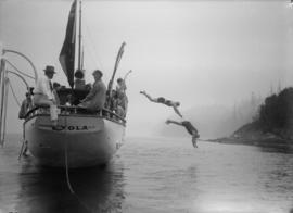 "People on the deck and swimmers diving off boat ""Myola"""