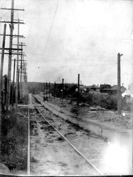 [View of a dirt road, possibly 33rd Avenue, with street car tracks along one side]