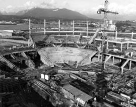 Construction of Pacific Coliseum, with view of North Shore mountains and Second Narrows Bridge