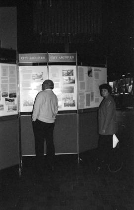 Man and woman viewing the Vancouver City Archives' display, Portholes and Pilings