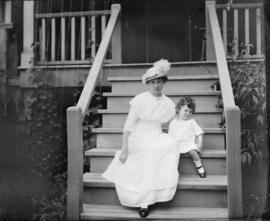 [A woman and child sitting on the steps of a house]