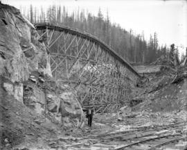 [Trestle across permanent spillway channel of Coquitlam Dam, carrying flume from the borrow pit t...