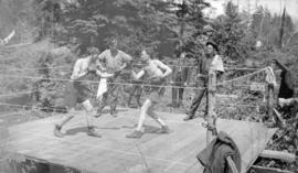 [Boys boxing in outdoor ring]