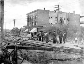 [Men laying bricks between rail tracks at] Main St and 17th Avenue [ in front of the Winram block]
