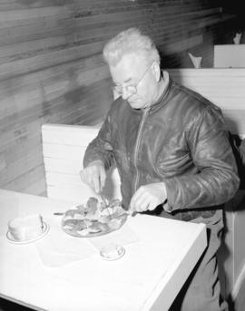 [A man eating oysters at] Oyster Bay