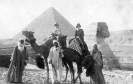 [Two women on camels with three men standing beside them]