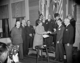 [Red Cross worker presenting a book to a man at a formal ceremony]