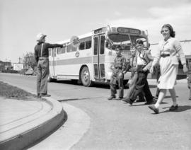 [School children crossing the street in front of a bus stopped by a school traffic control attend...