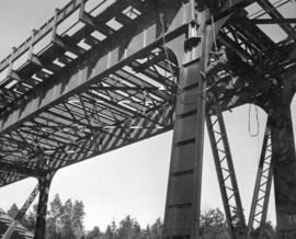 Painting quickly followed erection of steel.  Painter shown at work on North Shore viaduct using ...