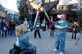 Two unidentified torchbearers passing the flame