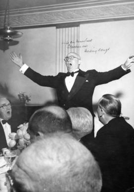 [Vice Air Marshall Stevenson leads the singing at The Honourable E.W. Hamber's birthday dinner]