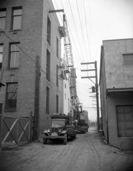 [Crane in an alley for telephone cable installations]