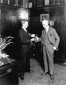 [Young man, possibly secretary George Fitch, presenting red tie to Mayor L.D. Taylor]