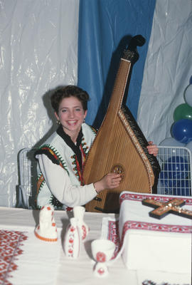 Woman holding a bandura at the Heritage Showcase during the Centennial Commission's Canada D...