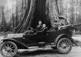 Cadillac and its occupants in front of the Big Hollow Tree in Stanley Park