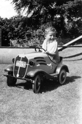 John Banfield in toy car on lawn