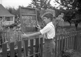 [Young boy making a chalkboard sign offering lawn mowing services]