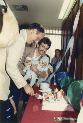 Mike Harcourt cutting cake beside Mr. Allan holding baby