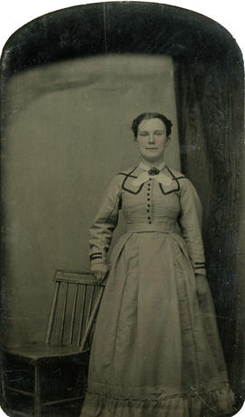 Portrait of unidentified woman standing by plain wood chair