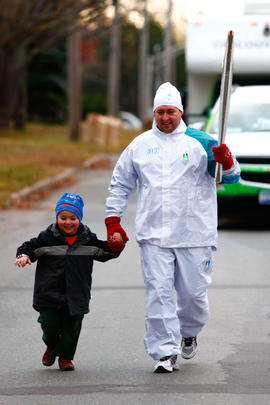 Day 24 Torchbearer 13 Chansey Veinotte runs the flame with his son in Vernon Bridge, Prince Edwar...