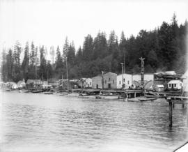 [Builders and totem poles along waterfront at Alert Bay]
