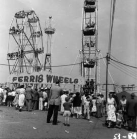 Crowd and Ferris wheels in P.N.E. Gayway