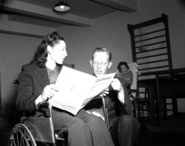 [Man with a woman in a wheelchair looking at a deed of land]