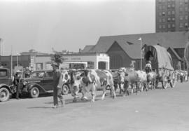 [Oxen pulling covered wagon in parade on Georgia Street west of Burrard Street]