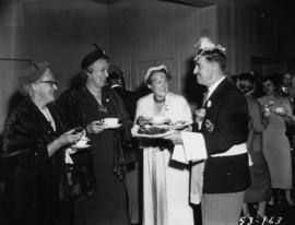 P.N.E. Vice-President J.C. Berry in maid costume serving snacks at tea party