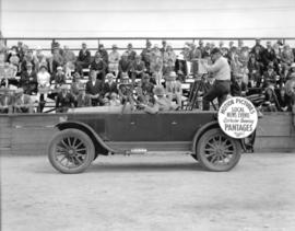 J. Errington [car with sign promoting Pantages news reels]