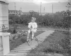 "[Jack Davidson on a tricycle in the backyard of ""Braeriach"" at 2119 West 42nd Avenue]"