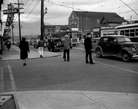 [Police officer, pedestrians, and traffic on Cambie Street near 12th Avenue]