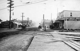 [View of Cedar Cottage Road (Commercial Street) at the B.C.E.R. tracks at18th Avenue]