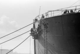 Men painting bow of ship