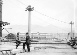 [Two men at partially constructed driveway at east end of C.P.R. station]
