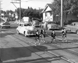[Girls in highland dance costumes march in front of a car advertising the Highland Games during a...
