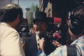 Press interviewing man in top hat