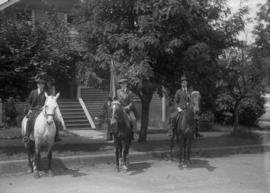 Three men on horses, one carrying a flag