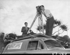 "Artray cameraman for KVOS TV's program ""at the P.N.E."" standing on car"