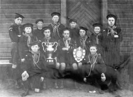 [Group portrait of sea scouts holding trophies]