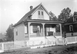 [Woman standing at front porch, and girl standing at front gate of house in Grandview-Cedar Cotta...